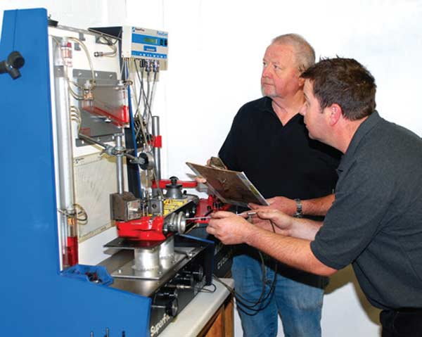 Fig. 3.1. Glyn Swift (left) and Nick Swift (right) are not just Swift in name. They build some of England's swiftest Mini Coopers, and it all starts here on the flow bench. This particular unit is a highly instrumented Super Flow 110.