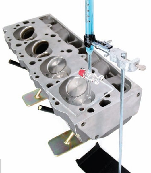 Determine combustion chamber volume by filling the chamber with water or alcohol from a graduated burette calibrated in cubic centimeters (cc). Tighten a spark plug in the chamber with both valves installed. Then use a light grease to seal the deck surface. Place the plastic cc plate over the chamber and position the head so the fill hole is at the highest point. Fill the chamber and read off the burette. Divide by 16.4 to convert to cubic inches.