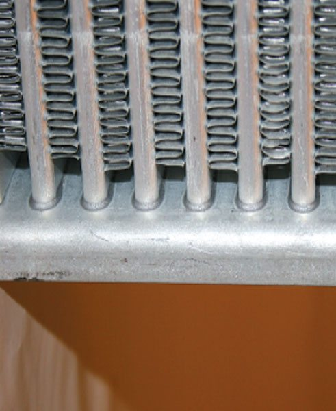 Tube and fin construction uses individual tubes that fit into a die-cut header plate and are furnace brazed to the header plate for air sealing and strength. (Courtesy Diesel Injection Service Company, Inc.)