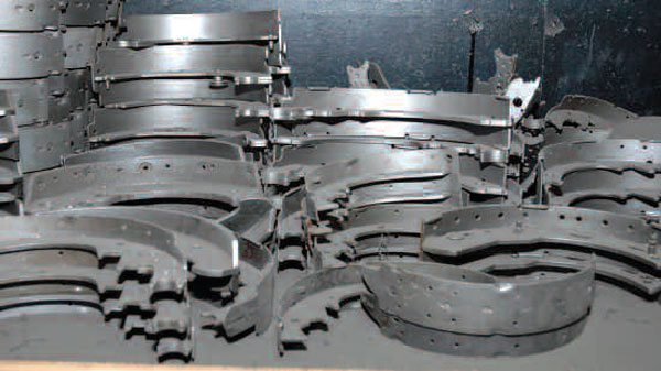 Many auto parts such as these brake shoes are made from stamped and machined mild steel. It's cheap, welds easily, and is available everywhere.