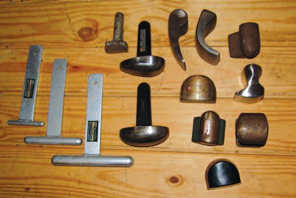 Dollies like these offer many useful surfaces for backing up hammer work. The three on the left are for working very small areas. The two larger dollies, with handles, can be mounted in vises and used in fabricating. The front dolly is rubber clad, and provides a somewhat resilient surface.