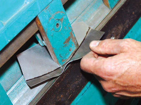 This finger or box-and-pan brake provides for bending around three-dimensional features of metal. It is shown here making a bend that would be impossible with a flat brake.