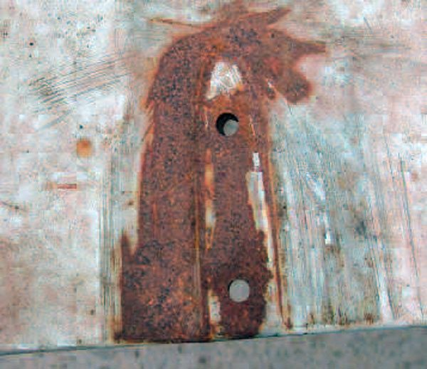 Before this repair was begun, the panel repair area looked like this. This photo was taken from the front of the panel. Note that the relief area was pushed down on the left, and the metal beyond that was sprung up and out from its edge.