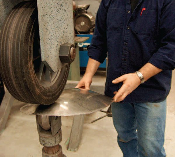 This imaginative wheel combination, mounted on an English wheel, uses a creasing lower wheel and a soft upper wheel, literally a caster wheel. The result is to allow forming without excessive stretching.