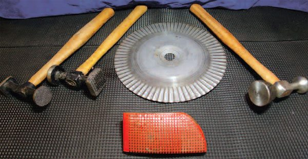 The serrated hammers (left) and the dolly (front) cause minor shrinking when they impact metal. The disc (center) causes heating and impact when it is rotated at high speed against metal, shrinking it. The hammer (right) employs a central face to hold metal and a rotating rim that gathers it.