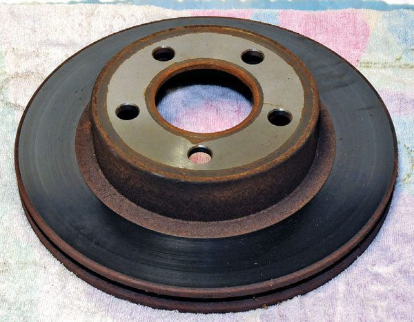 This old Subaru brake disc has cast-steel rust. The constant heating and cooling of parts such as this and their exposure to the elements lead them to rust quickly.