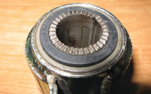 In contrast to the previous picture of a poly bushing, the center sleeve of this rubber bushing is non-removable. It's vulcanized to the rubber, and the rubber to the outside shell. Also the ends are serrated and extend past the bushing itself. This way, when the through bolt is tightened, the serrations dig into the frame mounts and prevent the sleeve from turning. It doesn't pivot. It deflects in torsion—the rubber twists. Polyurethane actually rotates around the center sleeve, which is why rubber doesn't need to be greased (no moving parts) and poly bushings do. (Photo Courtesy Tad Banzuelo)