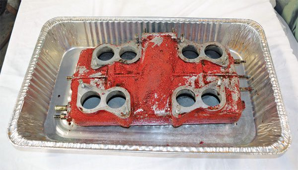 For a red wrinkle coat test project, I selected this intake plenum from a Ferrari 308. I stripped it with East-wood gel stripper and the old original paint came right off. I used a foil tray to contain the gel stripper and waste products.