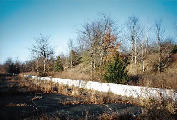 Although heavily overgrown, you can see the hillside that gave spectators a great view of the action. With most of the steel being used for scrap during the dismantling of the track, there isn't much left, aside from the pavement, the concrete walls, and the general landscape of the property. (Photo Courtesy Greg Friend)