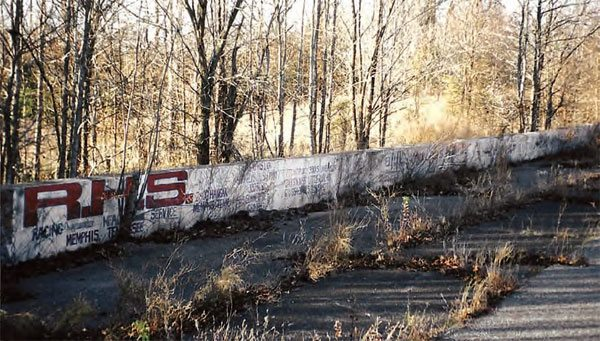 More painted signage survives on this stretch of the wall. Racing Head Service (RHS) was yet another Memphis-based company that eventually made it big. RHS is now owned by the Comp Performance Group, which is still based in Memphis. While the paint survives, the weeds and trees have taken over the asphalt racing surface. (Photo Courtesy Greg Friend)