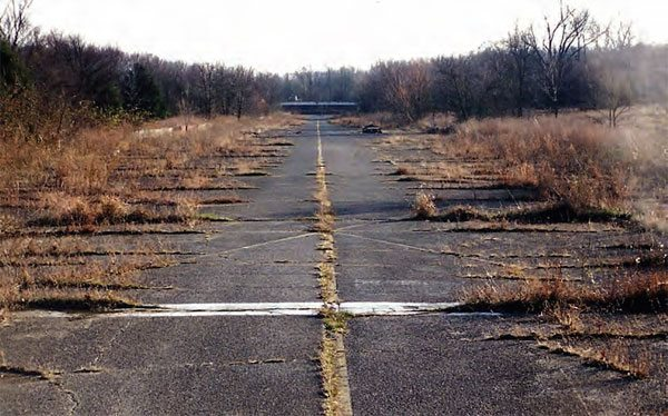 Standing at the finish line and looking toward the starting line, you can see that weeds are taking over the drag strip. Mass overgrowth will eventually swallow the historic race track, but the majority of the property remains intact. (Photo Courtesy Greg Friend)
