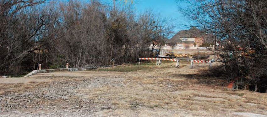 This concrete bridge is still intact, even after the major land development in 2005. The creek by the bridge was located behind the starting line. This portion of the track, as well as a small part of the pits, is still intact on one side of the subdivision. (Photo Courtesy Steve Scott)