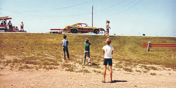 This view shows the track's landscape even better, as a few youngsters watch a funny car leave the line. The banked shoulders of the track made for an interesting ride if you veered off course, but steel guardrails protected the spectators. (Photo Courtesy Brent Fregin)