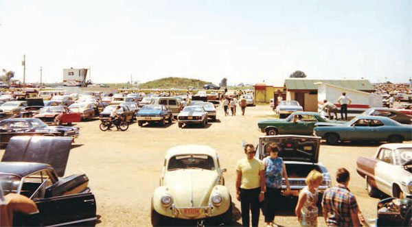 The unpaved pits weren't exactly luxurious, but that was part of the fun of racing at Oswego. You can see the simple timing tower on the left, with restrooms and concession stand on the right. Taken in 1970, this photo shows a diverse group of cars in the pits and parking area. (Photo Courtesy Brent Fregin)