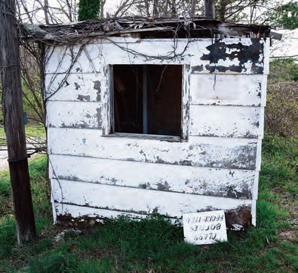 """The old ticket booth at the gate can still be found at the Hudson Drag Strip. The """"Glass Bottles Prohibited"""" sign has fallen off the building. It's amazing that no one has taken it for a souvenir, but the entire track seems to be untouched since its final race in 1994."""