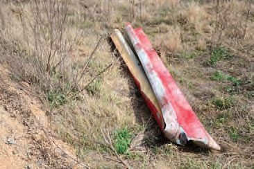 All of the steel guardrails have been removed from the track, but the wooden posts are still driven into the ground. During exploration of the track, I only found one piece of the track's guardrailing, which was known for its signature white-and-red paint scheme.