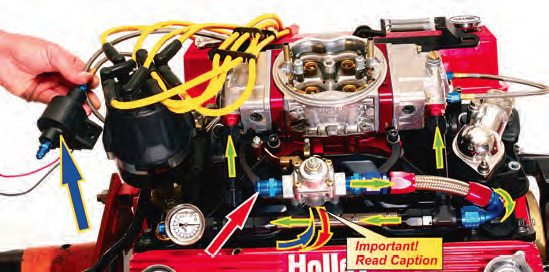 """This thermally controlled carb setup is not yet covered with insulating foam. Depending on the type of fuelpressure regulator being used (see Chapter 12), fuel either enters at the standard regulator or returns to the tank from the bypass regulator. If a standard regulator is used a fitting (red/white arrow) plugs the outlet. If a bypass regulator is used this is the """"fuel in"""" port via the cool can from the fuel pump. Although either type of regulator works, the best choice should be a standard regulator. Used in this manner the standard regulator never dead-heads the fuel pump because fuel is always being bypassed by virtue of the flow out of the fuel bowls. From the regulator, fuel is fed into the carb's fuel log and into the fuel bowls."""