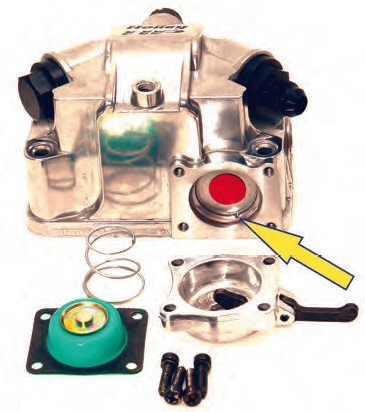 The pump comprises the parts shown here. The arrow indicates the discharge port that aligns with the port in the metering block.