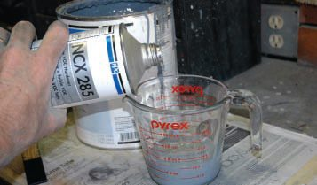 A large, glass kitchen mixing cup seems an obvious and convenient device for measuring paint, especially since it has a variety of ratio combinations printed on it. It is shown here with a 2:1 ratio of high-fill primer and catalyst, before stirring. The only problem—especially with today's sticky paints—is cleaning it after each use.