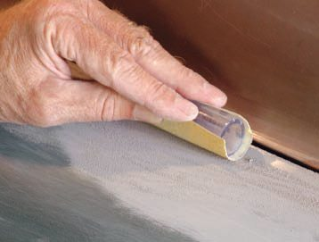 """For instance, this fender, which has been repaired and primed, has a convex surface on top—being sanded with 80-grit wrapped around a slightly pliable hard rubber squeegee—and a concave area next to the edge, calling for a short piece of heater hose as a """"block."""""""