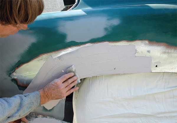 """In this case using a medium-size pliable plastic spreader, I apply the mixed filler quickly, but smoothly and evenly, to the dented area. One tip: when """"spreading"""" filler, don't just wipe it onto the surface, actually press it onto the metal to make sure it adheres."""