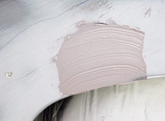 After the first board sanding with 36-grit, whether you had to hammer down some high spots or found a low spot or two—or both, apply another thin coat of filler either to those areas or over the whole area, and begin the process again.