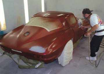 Individual painters have their own methods for spraying a car, but most start at the top and then work down and around. Starting the base-coat color, John has sprayed the top, and is working down the right door.