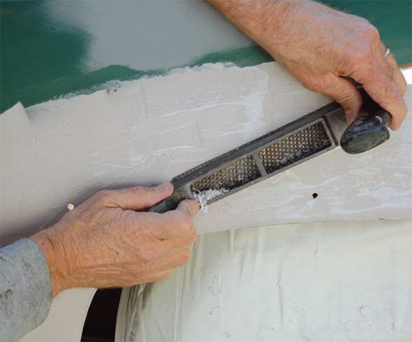 """If you've ever seen an article on bodywork, you've undoubtedly read that you should first shave the filler with a """"cheesegrater"""" blade. There's more to it than that. These perforated, sharpened, flat or rounded metal blades were first known by the Stanley trade name """"Surform,"""" and were invented to work, in appropriate holders, like a wood plane. They also work great for shaping or sculpting semi-soft sub-stances such as foam blanks for surfboards. But we don't want so much filler on your car that it needs sculpting or shaping. The purpose of the cheesegrater in the filler process is twofold—(1) to quickly """"knock down"""" (shave off) any rough edges, overlaps, etc. to smooth the surface, and (2), more importantly, to remove a sticky film that develops on the surface of the filler as it hardens. It's easiest to """"cheesegrate"""" the filler just before it fully hardens (when it's like hard rubber). The flat blades curve to a rounded surface (when not used in a holder); either flat or rounded blades can be used with or without a holder/handle. Pull the blade, without much down-pressure, in long sweeps, to shave the high spots off the filler. And even if the filler has hardened, you should """"cheesegrate"""" it; otherwise your sandpaper immediately clogs with sticky, small blobs of filler."""