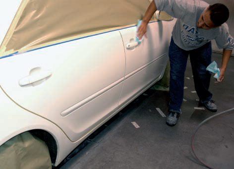 Once all the sanding and masking was done (note they used masking paper and tape to cover the wheels), they cleaned the whole surface with a silicone-remover (notice the dry rag in one hand to wipe off the cleaner before it dries), followed by a thorough wiping with a tack cloth.