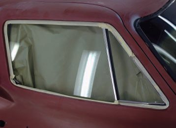 In some areas with tight corners, rubber moldings, and so on (such as this door window and vent), it's easier to run a piece of tape around it first, making sure it fits right next to the painted surface all around, then add the taped paper to this to cover the window.