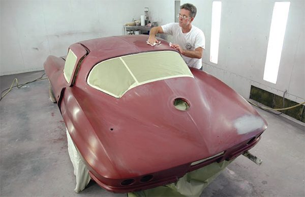 """Although we show several """"stages"""" of paint jobs in the following chapters (including more examples of masking), most typical at-home paint projects look like this when they're sanded, masked, and finally ready to spray. However, note that the trim, lights, handles, etc., are off, body openings are masked from the inside, chassis parts (i.e, exhaust pipes) are covered, as are wheels/tires, and the doors are ajar because interior openings are masked and the doorjambs will be painted along with the rest of the car."""