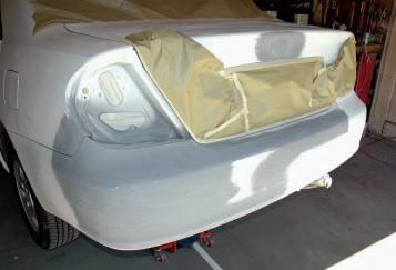 Then came more block sanding with 180-grit dry paper, followed by pad-sanding with 360-grit. Here we've done selective masking—over the chrome bar, license, lower trunk edge, good taillight, and even the exhaust pipe. Note the holes in the taillight housing taped from inside to keep paint out of the trunk, plus masking over the rear window to keep over-spray off. The rear wheel/tire was also covered before spot painting.