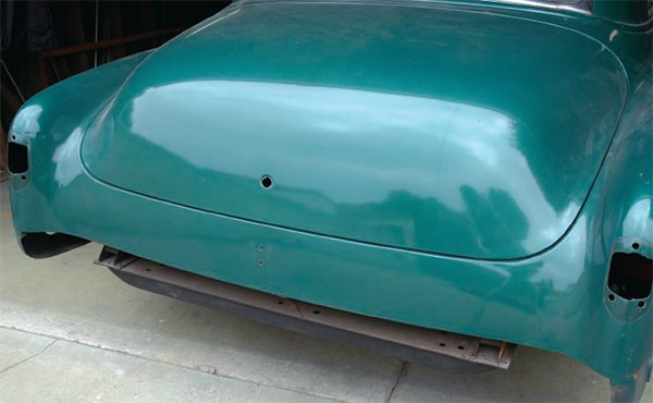 Let's use my '52 Chevy as an example of how you can use high-fill primer. We know this car only has factory paint, except where I've spotted it in with lacquer, such as here on the trunk, where I removed the handle/emblem, welded up the holes, ground them, then added a thin coat of filler and sanded it smooth before priming, spot painting, and rubbing it out. It looks okay here, but I could still see ripples in it after a few months' shrinkage.