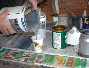 Fortunately, most paint products mix in ratio multiples of one. For instance, this high-fill primer should be mixed two parts paint to one part catalyst (no reducer). After thoroughly stirring the paint with the stick, I'm using the paper cup method (do not use plastic or Styrofoam; they can melt) to pour out two cups of paint...