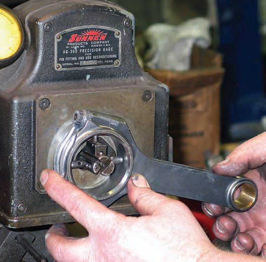 A rod bore gauge (the gauge shown here is on a Sunnen rod-honing machine) allows accurate and quick measurement of the rod-bearing bore diameter as well as allowing checking for bore runout. After calibrating the bore gauge to the desired bore diameter specification, the rod's big end is placed onto the gauge to verify bore diameter. This reveals whether the bore is correct, undersized, or oversized.