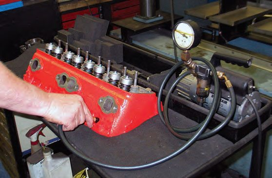 A bench vacuum tester allows testing for valve seating by applying vacuum to a spark plug port. Any drop in vacuum pressure indicates a poor seat seal.