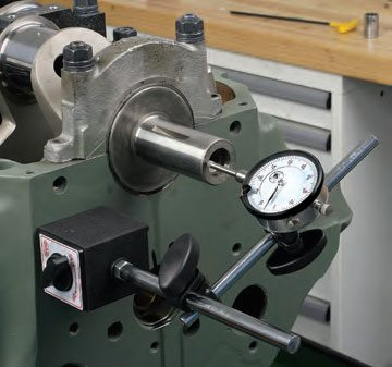 With the crank installed, place a dial indicator at a fixed position on the block, with the plunger contacting the crank nose or snout base. Using a flat-blade screwdriver (between a main cap and a counterweight), push the crank fully rearward. Preload the gauge to about .050 inch, then zero the gauge. Push the crank fully forward and note the gauge reading. This allows you to measure crank thrust. Repeat the procedure several times to verify your readings. Compare your thrust reading with specs. Crank thrust is usually somewhere around .006 to .007 inch.