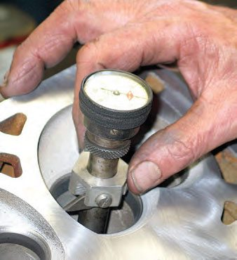 A runout gauge is used to check valve seat runout. A centering mandrel is inserted into the guide and the gauge is rotated along the valve seat. Any runout is unacceptable. This usually requires replacing the seat and cutting the new seat to establish zero runout.