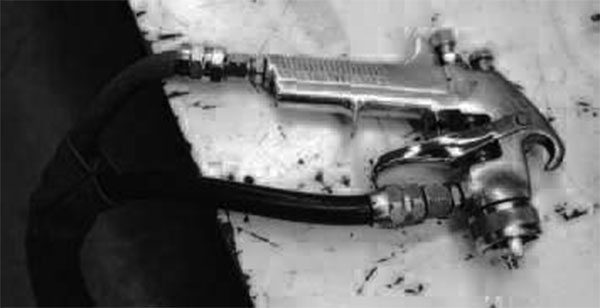 Even though it says DeVilbiss, this is not simply a paint spray gun pressed into service to shoot adhesive. DeVilbiss, among other manufacturers, makes a dedicated adhesive spray gun designed for easy cleanup and low adhesive buildup. While most home restorers won't find such a gun necessary, pros use them all the time.