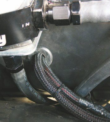 Fig. 5.35. Always use a rubber grommet or plastic snap bushing when running cables and/or harnesses through the firewall, even if they're loomed like these.