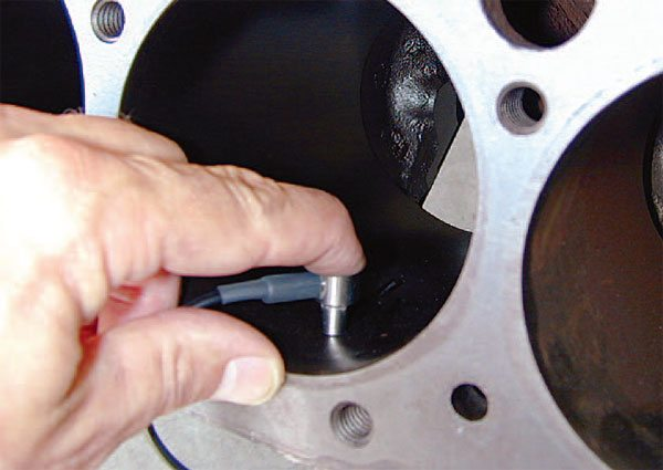 Sonic testing a race block's cylinder wall thickness at multiple points within each cylinder bore is the only accurate way to verify adequate cylin¬der wall thickness for any competition engine build. Here the engine builder is holding the sensor firmly against the cylinder wall to ensure an accurate reading. (Courtesy NDT Systems, Inc.)
