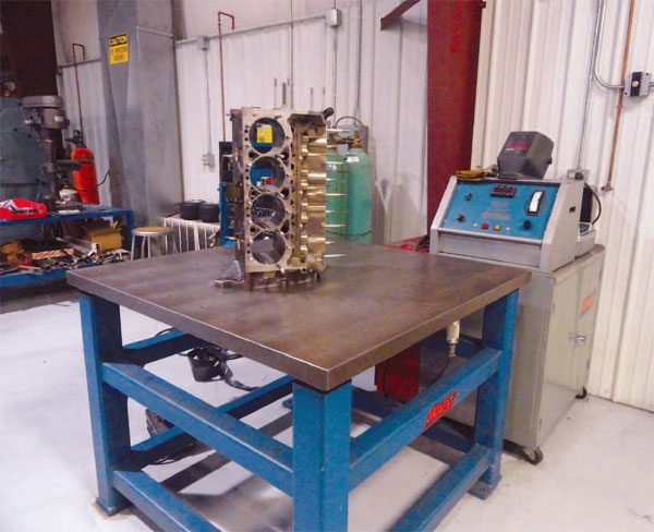 Top engine shops like Automotive Special¬ists leave no stone unturned to ensure maximum power and durability for engine customers. Here a MetaLax vibratory table from Bonal Industries is used to vibrate engine components outside their natural frequency to remove stress. (Courtesy Auto¬motive Specialists)