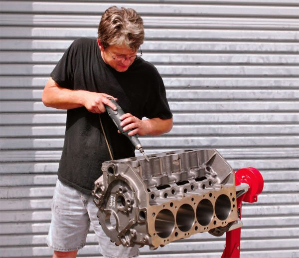 Carefully inspecting and deburring the cylinder block is the first step in any com¬petition engine build. The deburring process removes all sharp edges and casting flash. It also includes chamfering the freeze plug holes and break¬ing the leading edge of each cam bearing bore to facilitate the easy installation of the cam bearings.